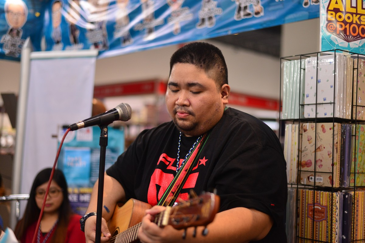 Mark Mirabuenos, one of the writers of Take Heart, performing an original song